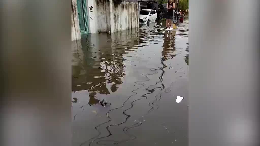 Khách Tây chèo ván lướt sóng trên đường phố ngập lũ ở Bali