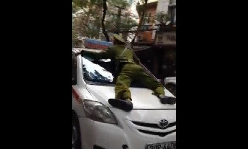Cop drives on taxi's hood in Hanoi