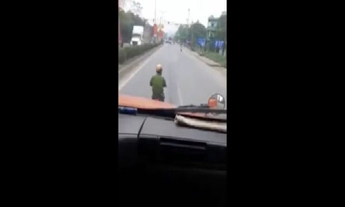 Vietnam cop uses cellphone during road ride