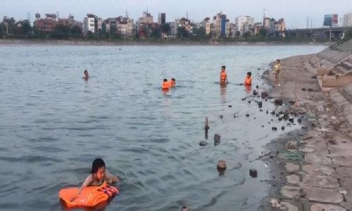 Locals in Hanoi bath in Linh Dam Lake