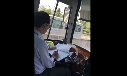 Video shows Vietnamese bus driver busy with paperwork on highway