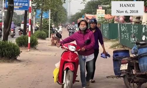 Hanoians walk motorbikes on sidewalk to avoid rush hour traffic