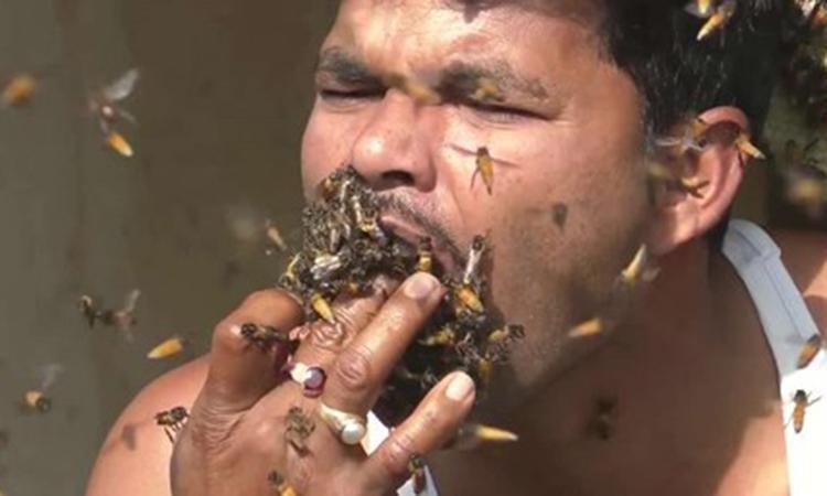 Người đàn ông nhốt ong vào miệng để lấy mật