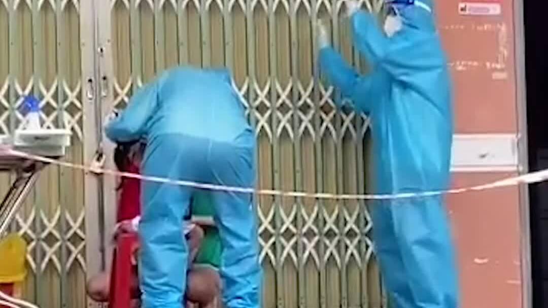 Tình nguyện viên nhún nhảy để động viên bé gái lấy mẫu xét nghiệm Covid-19