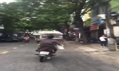 Người đàn ông vừa lái xe vừa chở hàng trên đầu trên phố Đà Nẵng