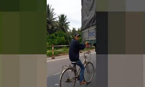 Thanh niên chạy xe đạp núp sau ôtô tải