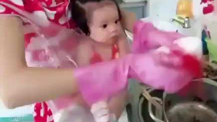 Mẹ địu con trước ngực bằng túi nilon để rửa bát