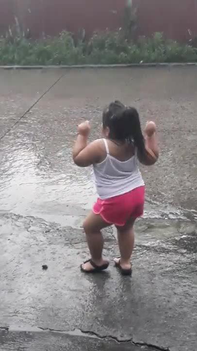 Bé gái cao hứng, nhún nhảy dưới mưa như vũ công chuyên nghiệp