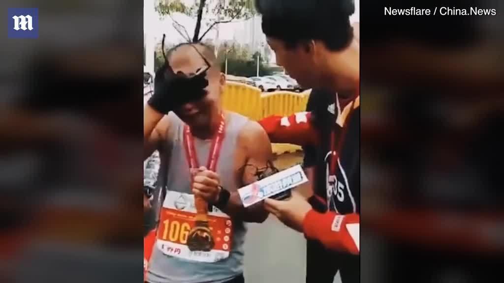 Ông bố bật khóc khi cầm ảnh con trai đã mất cán đích cuộc thi chạy