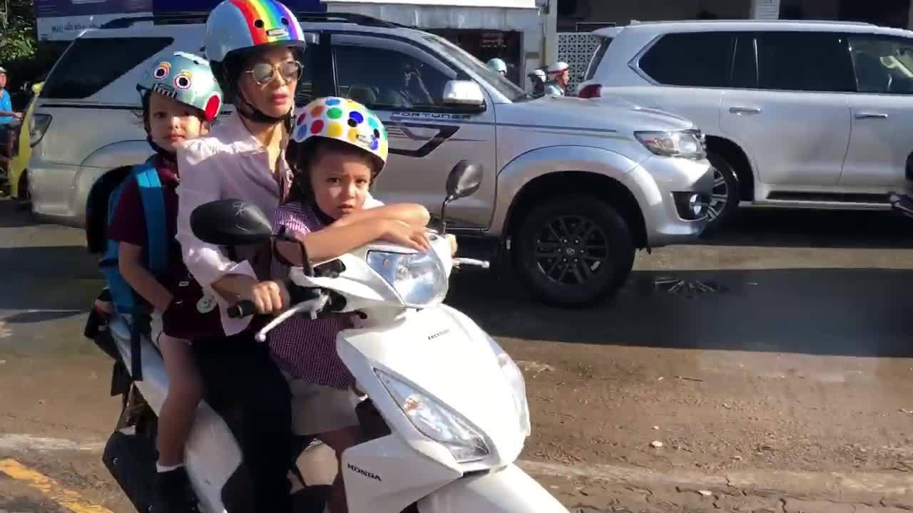 Hồng Nhung tự chạy xe máy chở hai con đến trường