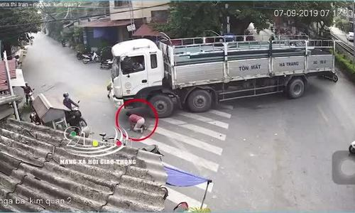 Người phụ nữ lao ra nằm dưới bánh xe tải