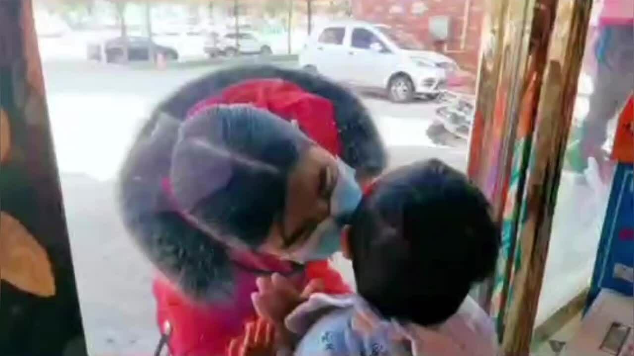Y tá thơm con trai qua cửa kính