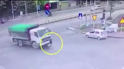 Cô gái đi giữa đường bị xe tải cuốn vào gầm
