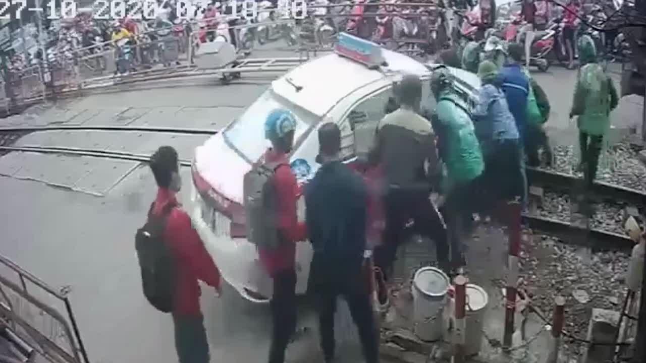 Người dân nỗ lực giải cứu taxi bị mắc kẹt khi cố lao qua rào chắn
