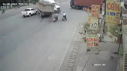 Hai người đi xe máy thoát chết trong gang tấc trước đầu xe tải