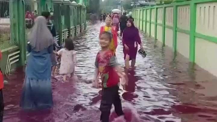 Nước lũ màu đỏ tràn vào ngôi làng ở Indonesia