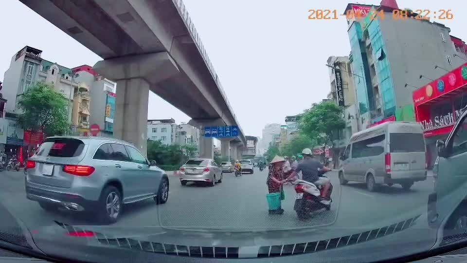 Người đi xe máy dắt tay cụ bà sang đường
