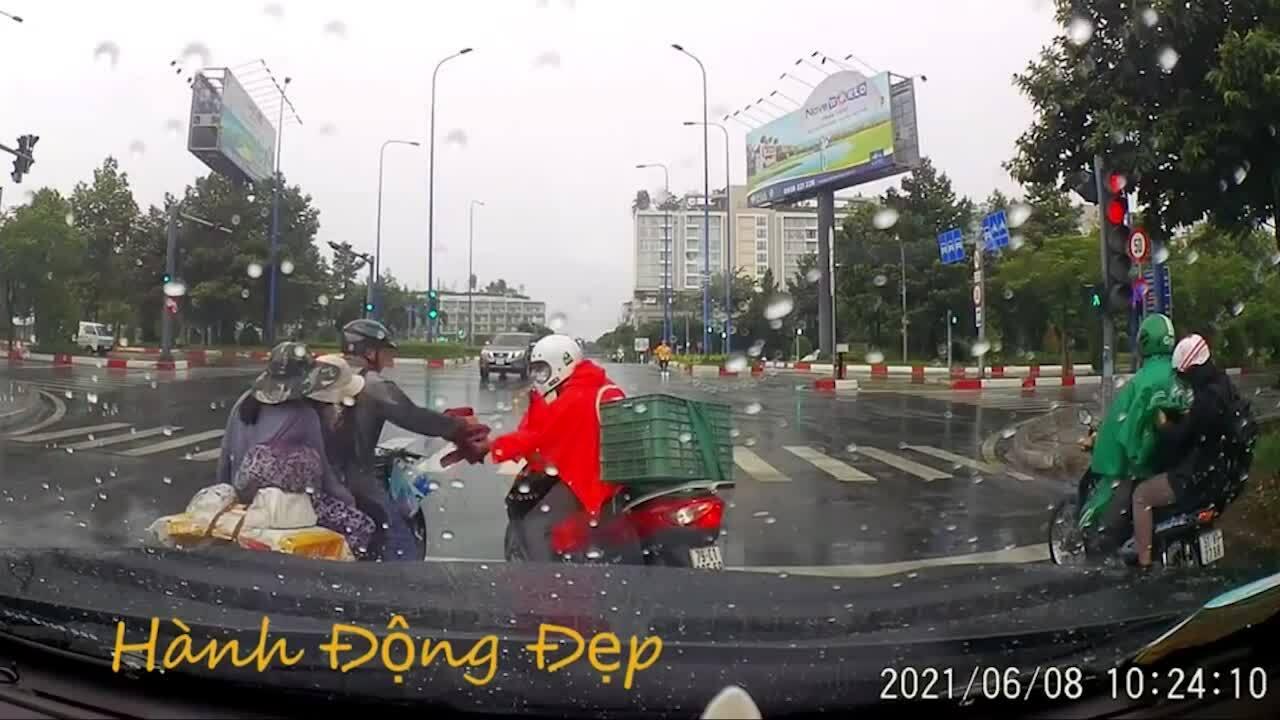 Chàng trai tặng áo mưa cho gia đình trên phố Sài Gòn