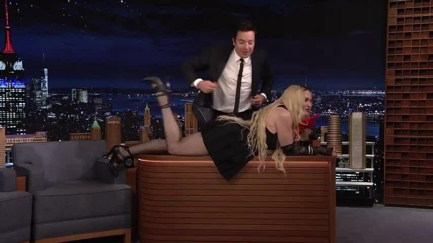Madonna nằm dài trên bàn trêu chọc MC