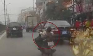 Quái xế nằm trên yên lái xe máy ở Hà Nội