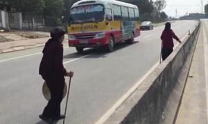 3 cụ bà chống gậy trèo qua dải phân cách quốc lộ 1A