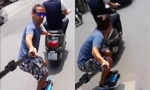 Người đàn ông Tây bám xe máy, trượt ván trên phố Hà Nội