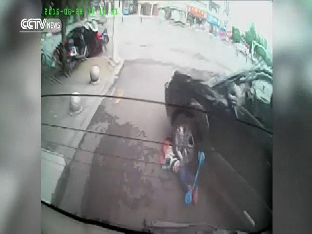 Ôtô chèn lên người bé trai đứng giữa đường
