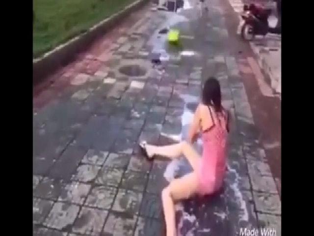 Cô gái bị đẩy ngã lộn nhào khi tắm gội ngay trên đường