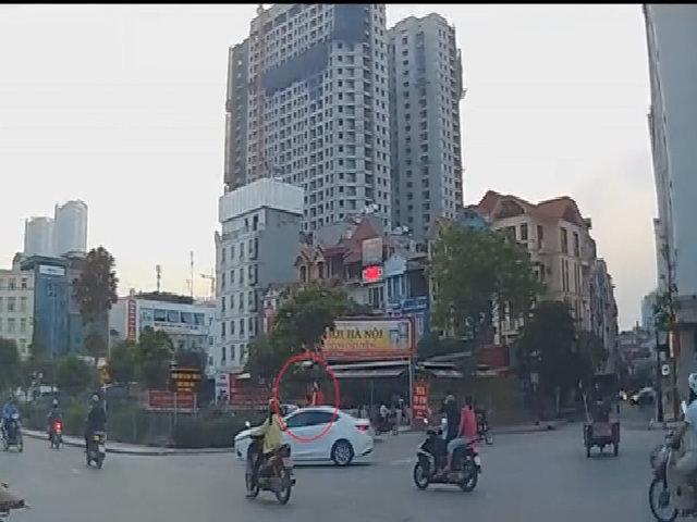Hai bé gái ngồi vắt vẻo trên nóc ôtô giữa phố Hà Nội