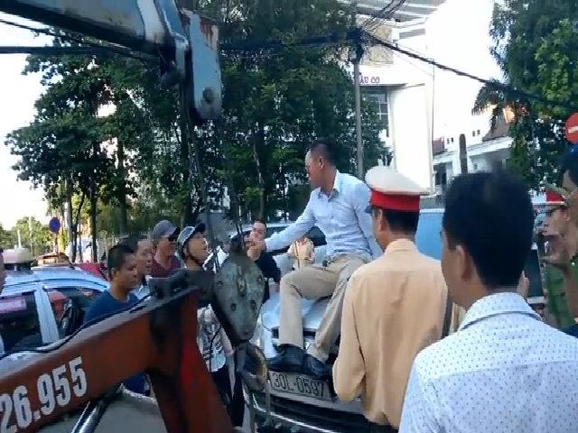 Tài xế ngồi lên nắp capô phản đối cảnh sát cẩu xe