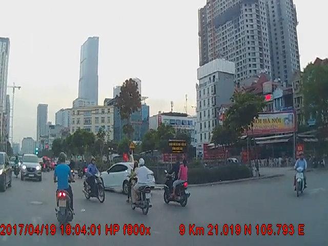 Hai bé gái ngồi vắt vẻo trên nóc ôtô chạy giữa phố Hà Nội