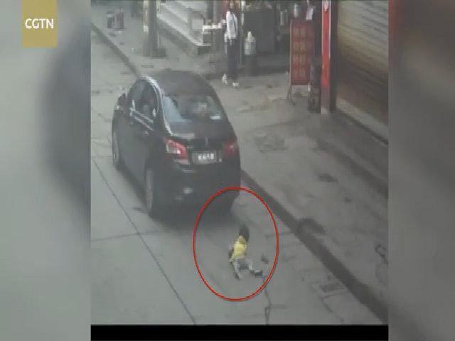 Bé gái sang đường một mình bị ôtô chèn lên người