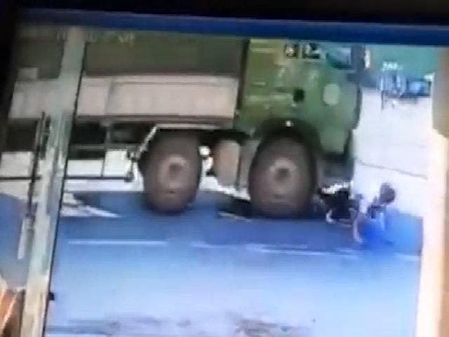 Hai người đứng dậy bước đi dù bị xe tải cuốn vào gầm