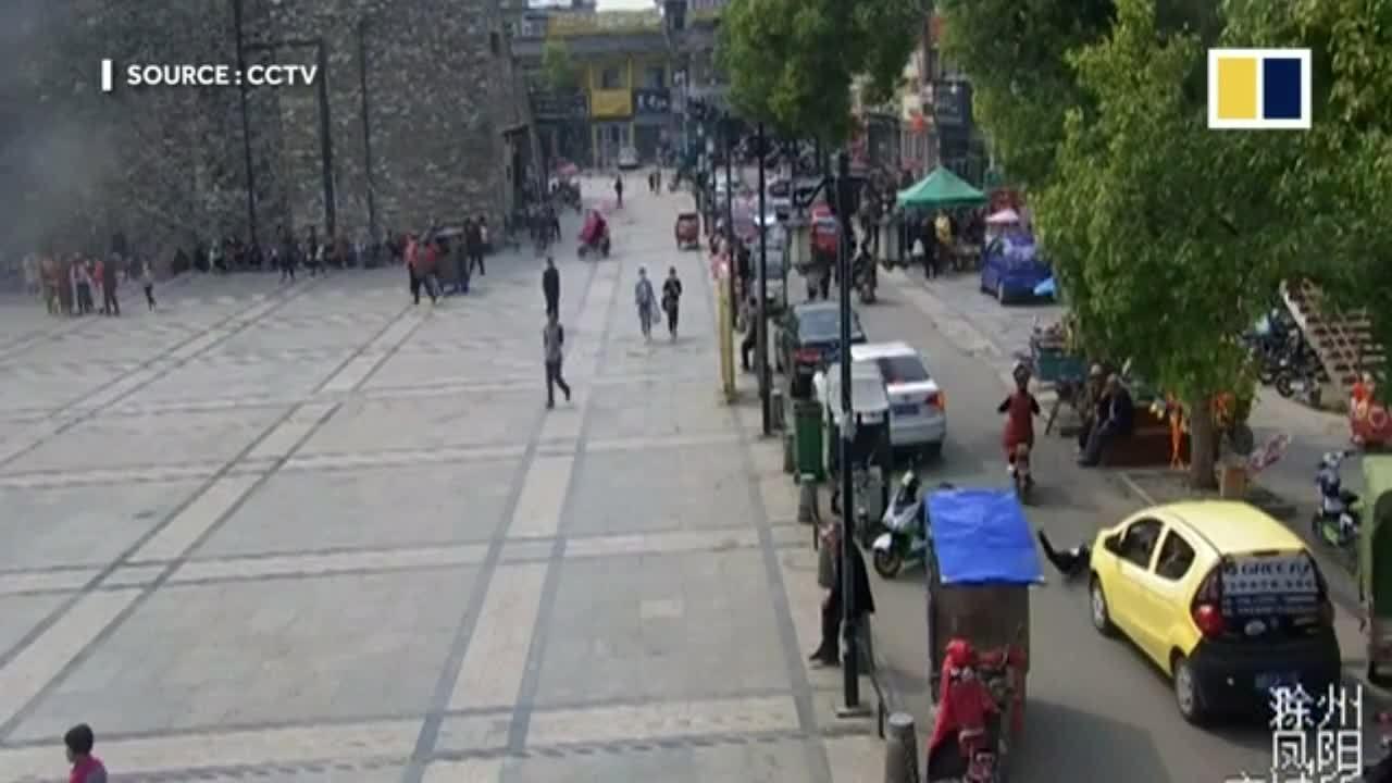 Bé trai Trung Quốc ngồi sau xe đạp điện bị ôtô chèn qua