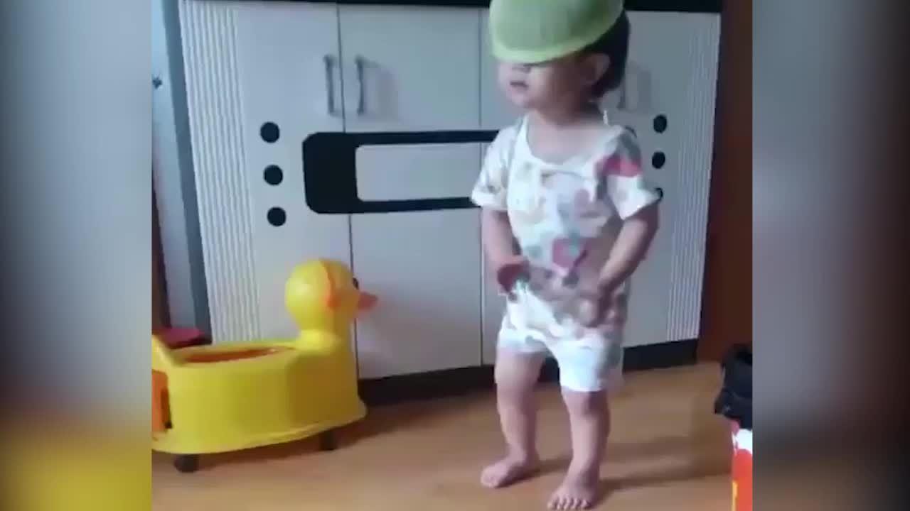 Bé trai vừa đội rổ vừa nhảy múa