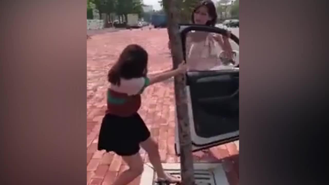 Hai cô gái luống cuống khi cửa ô tô bị vướng vào thân cây