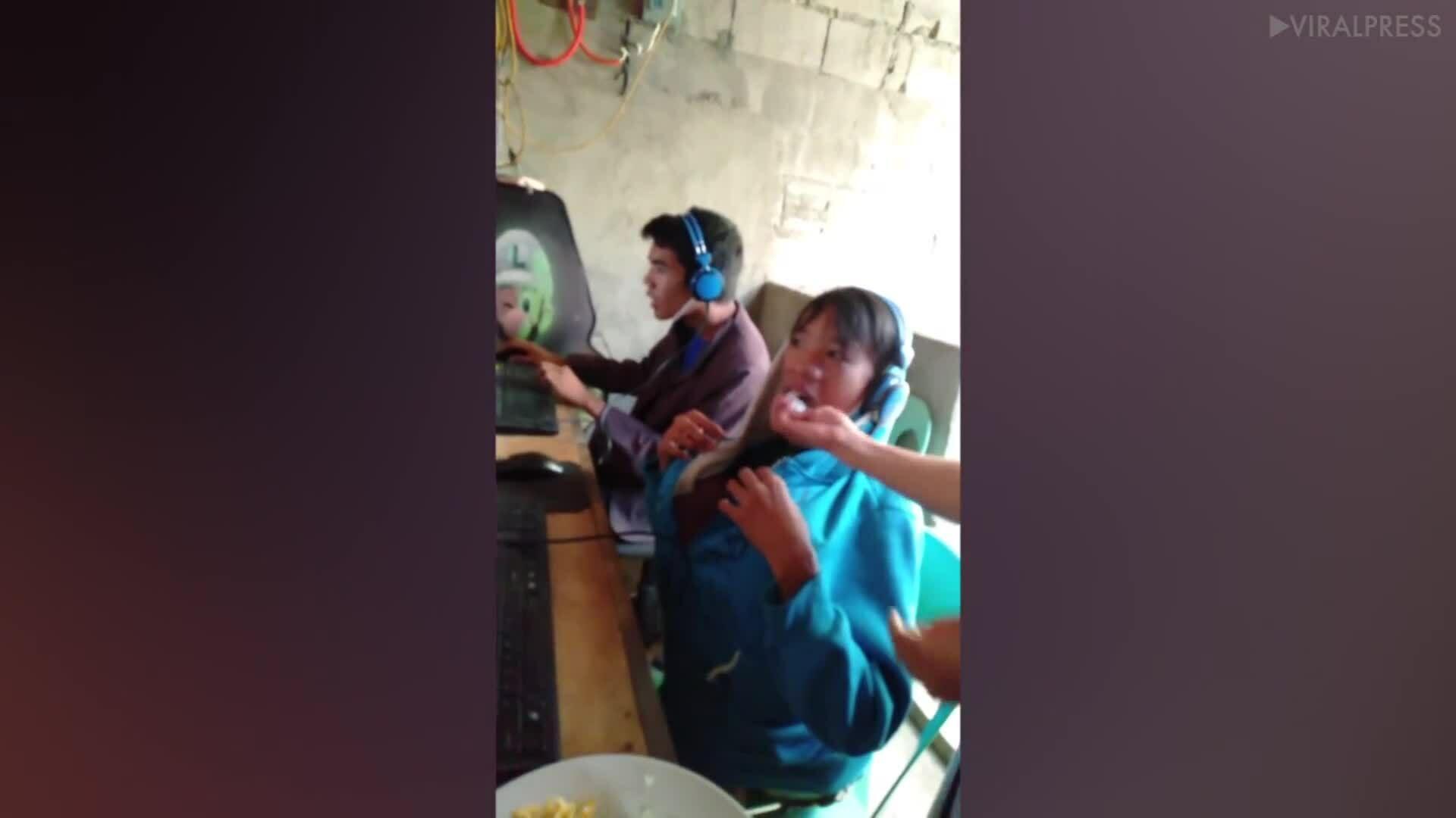 Cậu bé Philippines được mẹ bón cho ăn khi chơi game
