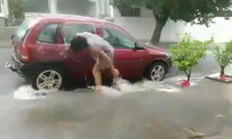 Người phụ nữ tranh thủ rửa xe dưới trời mưa