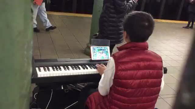 Cậu bé chơi game trong lúc đánh piano trên đường ở Mỹ