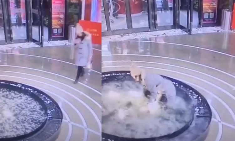 Cô gái ngã vào bể nước vì mải nhìn điện thoại