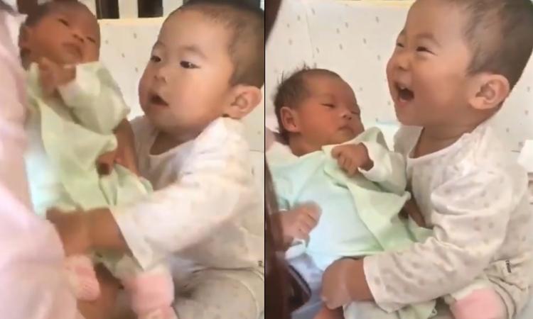 Cậu bé cười tít mắt khi được bế em mới sinh
