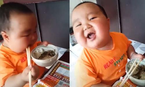 Cậu bé bưng bát cơm rau ăn ngon lành