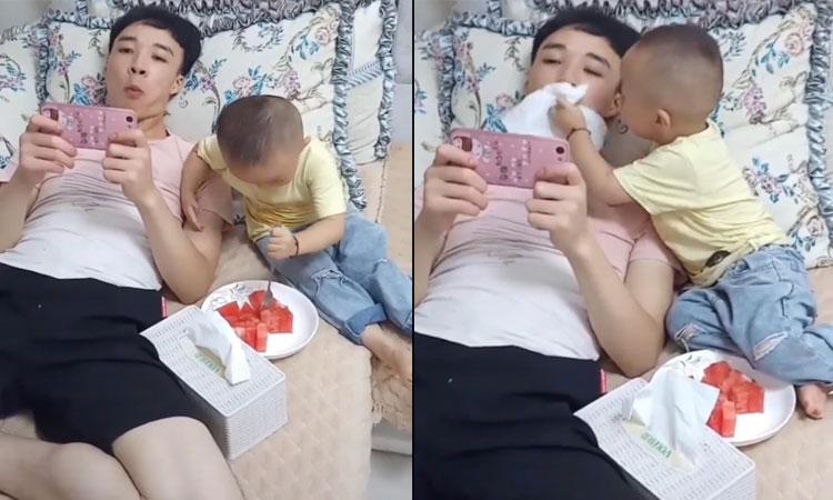 Cậu bé tận tình đút trái cây cho bố ăn