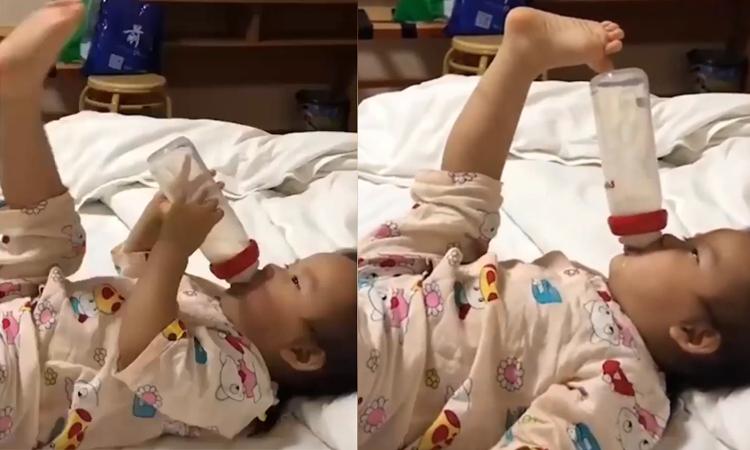 Em bé dùng chân đỡ bình sữa