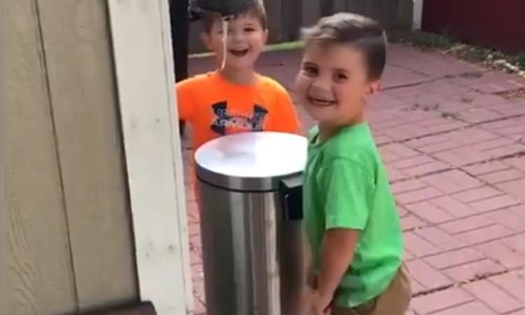 Hai cậu bé hớn hở khi chơi đùa với thùng rác