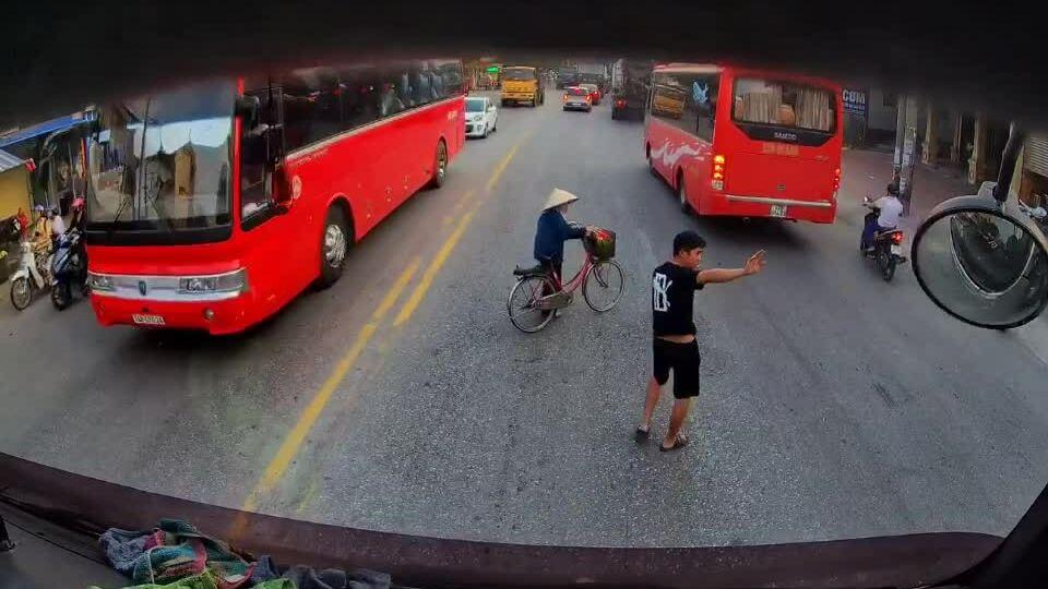 Tài xế container giúp cụ bà dắt xe đạp sang đường