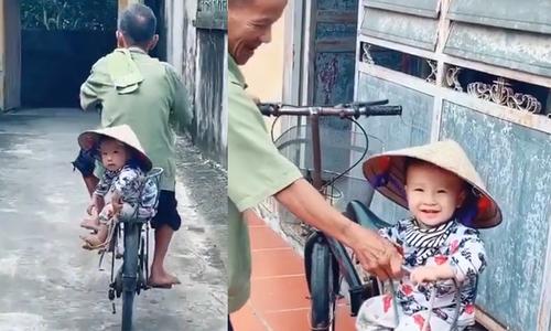 Em bé cười tươi khi được ông đèo trên xe đạp