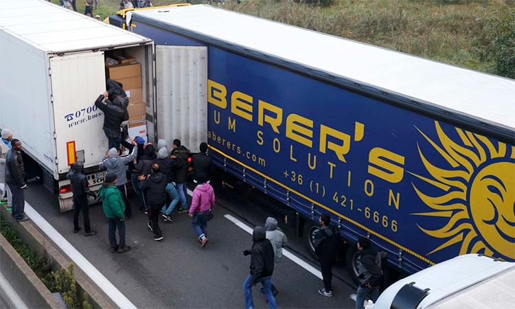 Người nhập cư nhảy lên xe tải đang chạy để vào Anh
