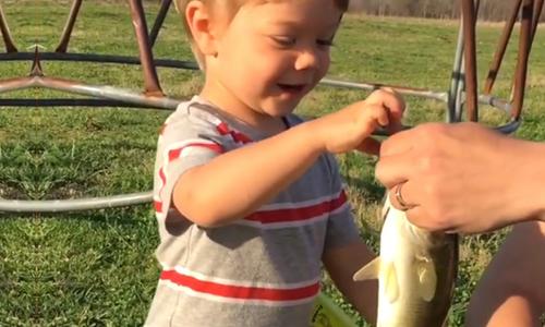 Cậu bé cười tít mắt khi cá cắn câu