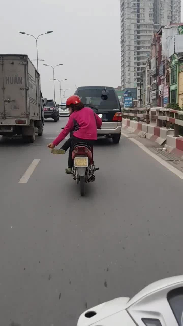 Người phụ nữ vắt chân chữ ngũ điều khiển xe máy